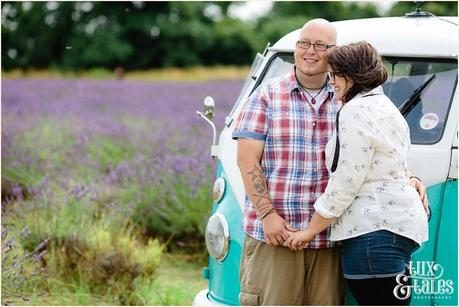 Couple cuddle in front of VW camper van in UK lavender field mayfield