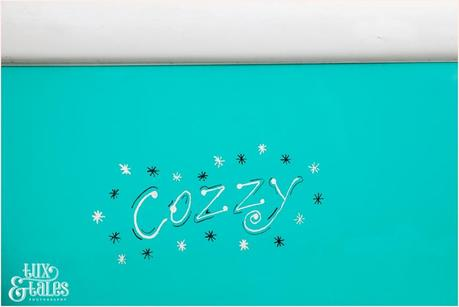 Script text that says Cozzy on a teal vintage camper van