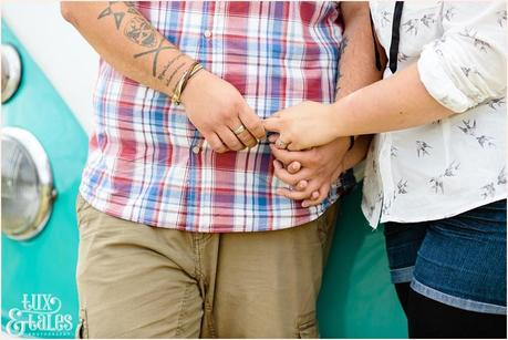 Tattooed rocker couple hold hands in UK engagement shoot he is wearing a checked shirt