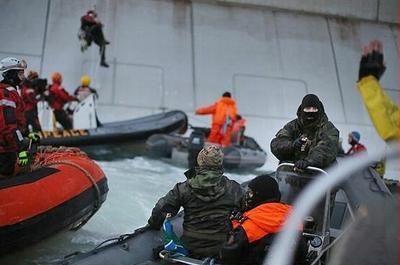 Russian Coast Guard officer, right, points a gun at a Greenpeace activist with raised hands, while another activist dangles on a rope from the Gazprom oil rig Prirazlomnaya, September 18, 2013 (Photo by Denis Sinyakov / Greenpeace)