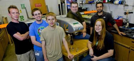 A team of Clarkson engineering students and staff pose with the Golden Eagle, an unmanned aerial vehicle constructed last year. The parts in the foreground will go on the new UAV the team is designing. In the front row, from left to right: Jacob T. Miller, Sean Shea, Ryan Feldman, and Cassandra Christman. In the back, Dan Valyou, left, a senior specialist in Clarkson's Civil and Environmental Engineering Department, and Omer Bakshi. (Credit: Clarkson University)
