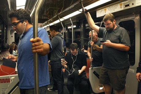 Brandon Long (right) is among the many commuters using smartphones on the way to work on a Muni train stopping at San Francisco's Powell Street Station on Friday. Photo: Liz Hafalia, The Chronicle