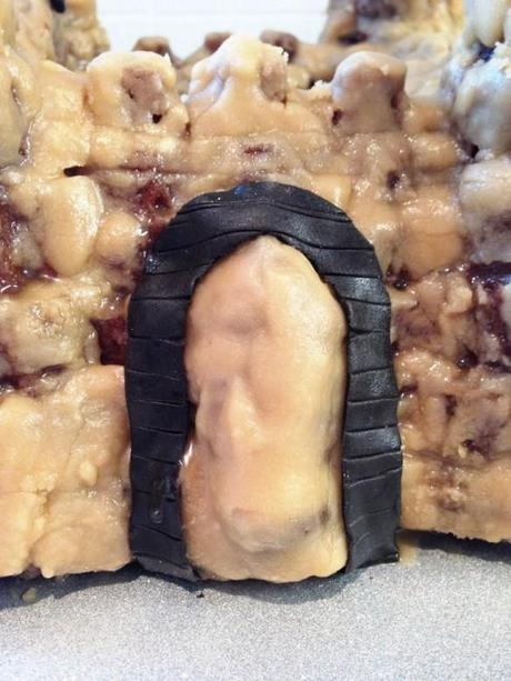black chocolate fondant archway on castle cake brickwork detail sticky caramel icing frosting
