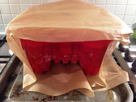 covering silicon castle cake mould in greaseproof paper for long baking time to ensure no burning
