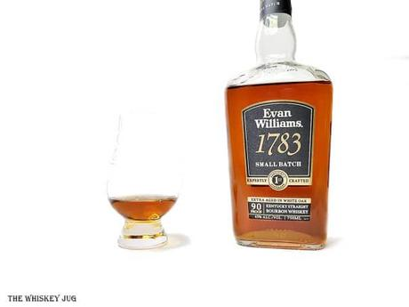 White background tasting shot with the Evan Williams 1783 Small Batch bottle and a glass of whiskey next to it.