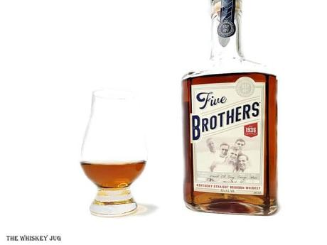 White background tasting shot with the Five Brothers Bourbon bottle and a glass of whiskey next to it.