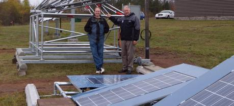 Michigan Tech solar energy scientist Joshua Pearce, left, and Jay Meldrum, director of the Keweenaw Research Center, with the array of solar panels behind KRC. Even on this gloomy day, they were cranking out electricity.