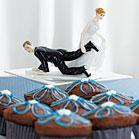 A funny cake topper with an bride carrying the groom by the leg