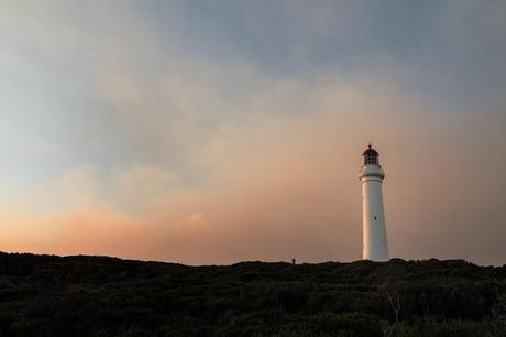 split point lighthouse sunset with thick smoke in sky