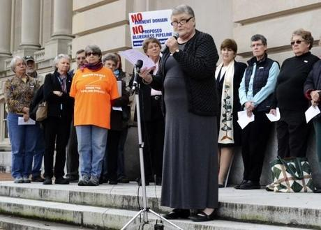 Rev. Mary Love of Crescent Hill Presbyterian Church speaks to demonstrators on the steps of the Kentucky Capitol building on Tuesday.