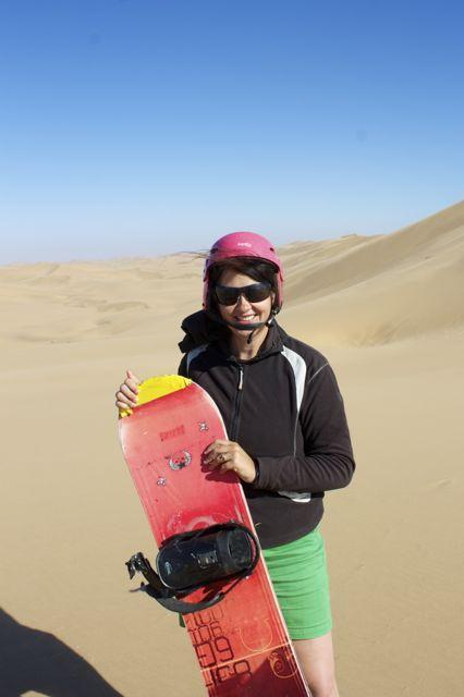Laurel Robbins posing with her sandboard in Namibia.