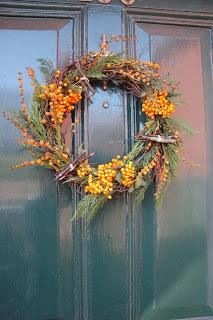 Yellow cotoneaster berries, mossy twig bundles and crocosmia seed heads decorate this pine and willow wreath.
