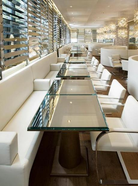 Simone Design Blog|Commercial interiors that are inspiring with its color scheme|Restaurant is decorated in white and gold. The glass table tops and pendant lighting complements the modern look of the room.