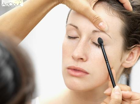 Woman having eye shadow applied