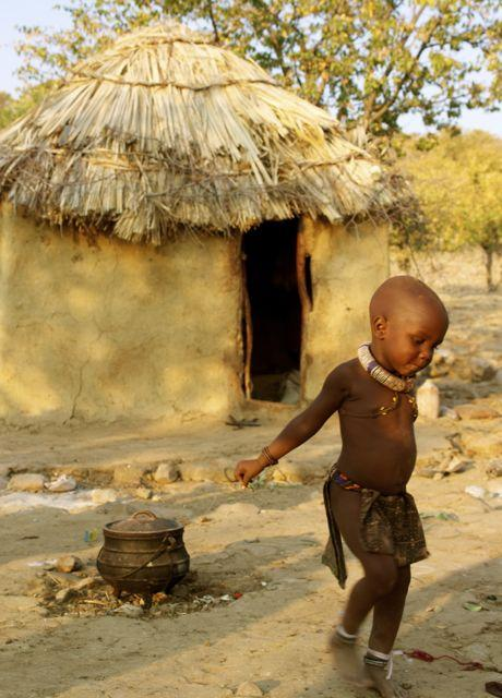 Child dancing in front of a hut in the Kunene Region of Namibia