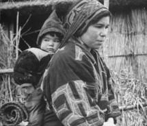 Ainu woman and baby in traditional garb,.