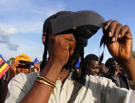 Man photographing solar eclipse, Uganda