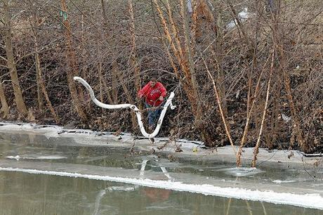 A Freedom Industries worker places boom in the Elk River at the site of the chemical spill