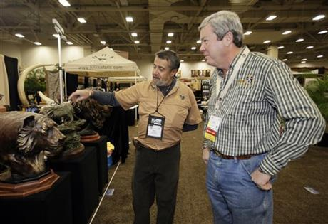 Dallas Safari Club executive director Ben Carter, right, talks with wildlife artist Raj S. Paul at his exhibit booth in the Dallas Convention Center as preparations continue for the clubs weekend show, Wednesday, Jan. 8, 2014, in Dallas. The FBI is investigating death threats made against members of the Dallas Safari Club, which intends to auction off a rare permit to hunt an endangered black rhino, an FBI spokeswoman said Wednesday