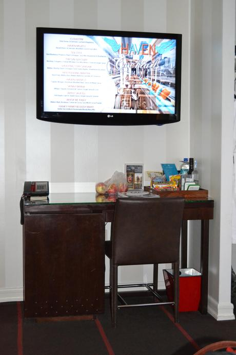 Wall TV with a desk and mini fridge