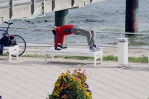 Man in athletic clothing doing reverse table on an outdoor bench.