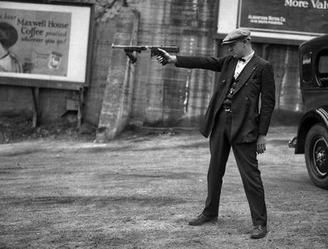 In this 1927 photograph, Lt. Oscar Bayer of the LAPD Detective Bureau aims a Thompson with a removed stock (and no magazine) for demonstration purposes. The Dillinger gang modified their Thompsons this way, but as this photo pre-dated Dillinger's spree by six years, they were clearly not the first to do so.
