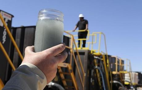 A jar holding waste water from hydraulic fracturing is held up to the light at a recycling site in Midland, Texas, Sept. 24, 2013. With fresh water not as plentiful companies have been looking for ways to recycle their waste. CREDIT: AP Photo/Pat Sullivan