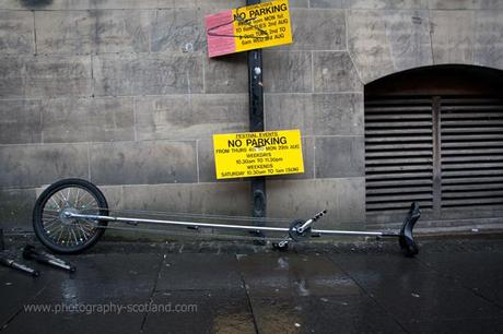 Photo - a unicycle left in front of a 'no parking' sign at Edinburgh's Fringe Festival