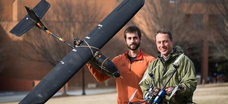 Wake Forest biology graduate student Max Messinger and biology professor Miles Silman pose with their remote controlled helicopter and fixed-wing aircraft on Davis Field