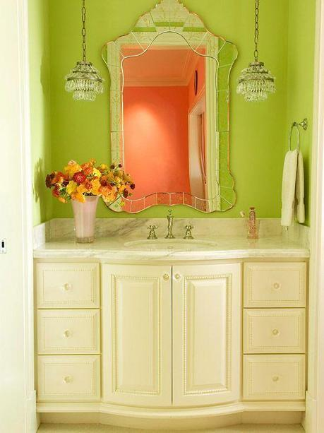 The antique inspired vanity, mirror, and hanging pendants combined with bright colored walls pull this tight elegant space together with some savvy style.