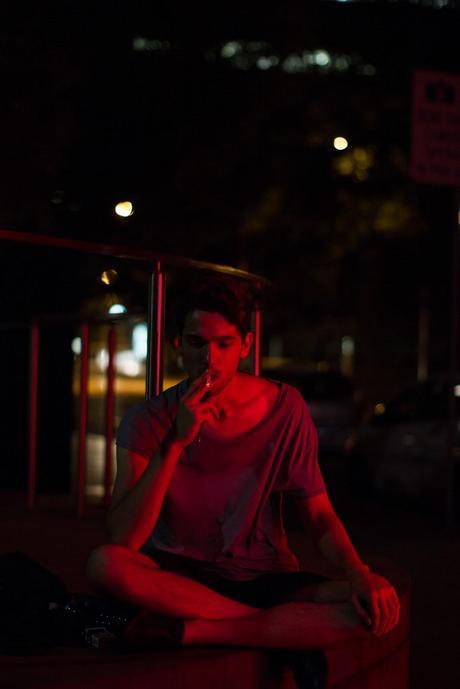 man smoking at night under red light