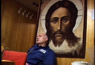 Christ in Russian sub. This commander is taking a break in the rec room for the crew, sitting beneath the print of a famous Orthodox icon of Christ. And, he's not in just any sub. He's in a Typhoon class, the kind written about in