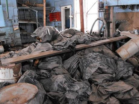 This photo taken on March 3, 2014, and provided by the North Dakota Health Department, shows bags full of radioactive oil filter socks, the nets that strain liquids during the oil production process, piled in an abandoned building in Noonan, North Dakota.