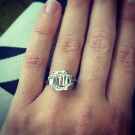 Three stone emerald cut engagement ring with trapezoids