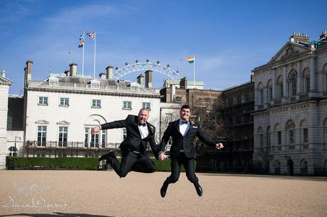Gay couple jumping in front of gay pride flag