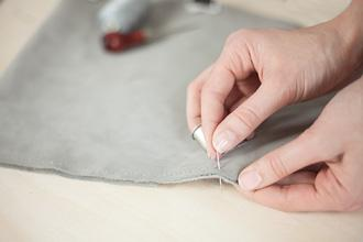 hand stitching a DIY tablet case