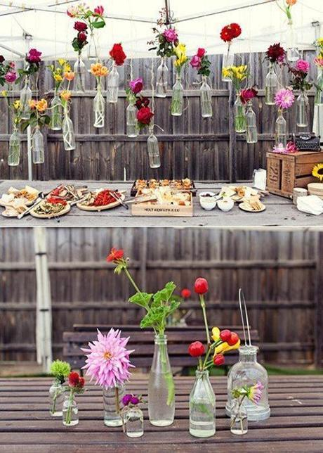 Flowers in Bottles Hung On Fence