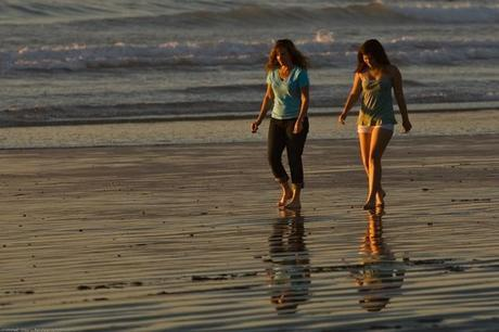 A Mother Daughter team (presumably) walk barefoot together on the beach