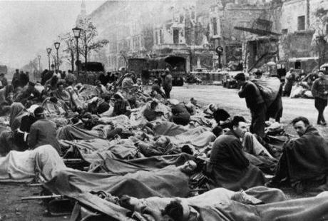 Vast throngs of wounded German soldiers crowd the streets as nurses attend to them.