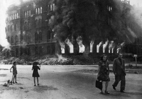 A German couple strolls past a burning building. Bizarre scenes like this were common at this time and place.
