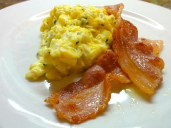 Scrambled eggs, prepared with herbs, and served with bacon.
