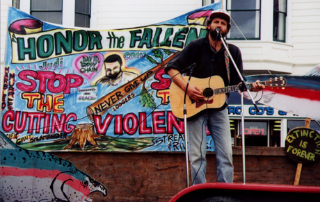 Albion communard plays guitar at rally (circa 2001, courtesy of EF! Journal archive)