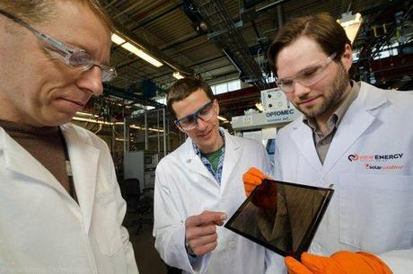 Dr. Scott Hammond (right) and NREL researchers examining a grey-brown tinted SolarWindow module