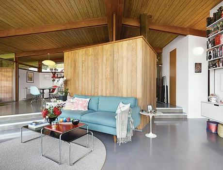 Wood paneled living room in renovated midcentury modern home in Los Angeles with blue couch and Marcel Breuer tables.