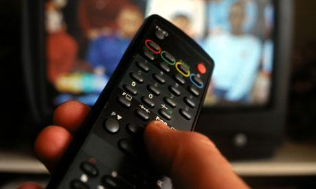 Hand holding TV remote control with television in background
