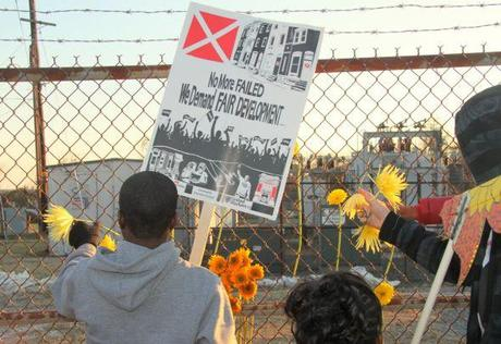 In December, students left flowers at the fence of a former chemical plant in South Baltimore where a trash incinerator is proposed. Photo by: Fern Shen