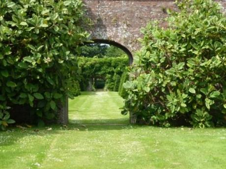 mature shrubs aside garden archway at Petworth