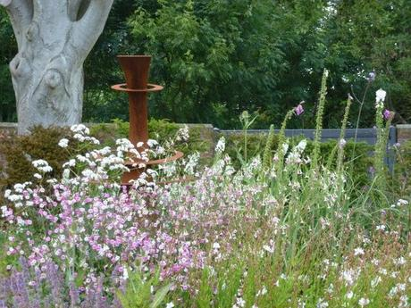 grasses in the foreground and a corten steel feature in the background