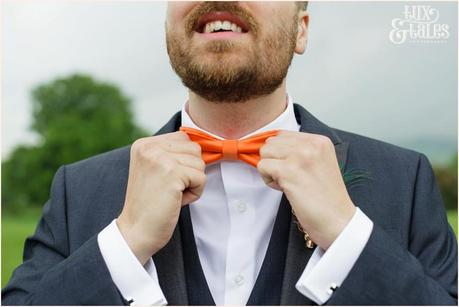 Groom adjusts bow tie at yorkshire sculpture park wedding