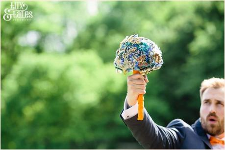 Groom holds up brooch bouquet yorkshire sculpture park wedding